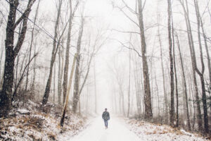 Man walking down a snow covered road of representing individual counselling in Calgary.