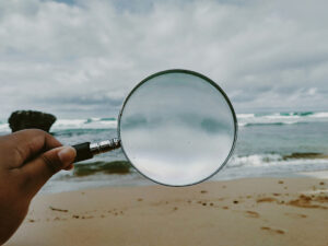 calgary counselling service client holding magnifying glass on beach