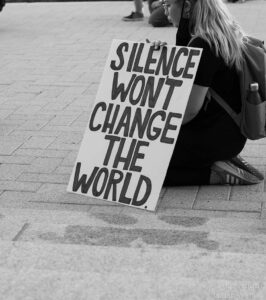 grayscale photo of girl holding sign at protest