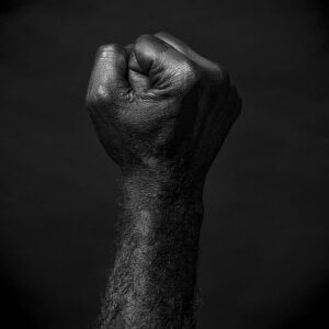 grayscale photo of raised fist of rage