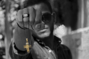 grayscale photo of televangelist wearing sunglasses holding gold cross with huge diamond ring