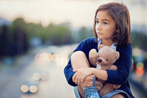 calgary depression support image of childhood trauma showing a young girl clutching a teddy bear for comfort