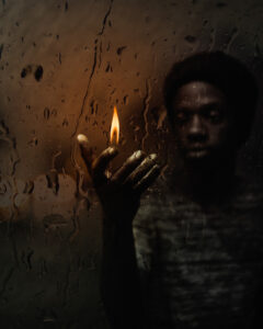 man holding lit candle