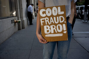 person in gray and blue shirt and blue denim jeans with cool fraud bro sign