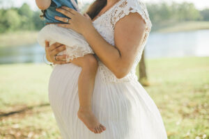 pregnant woman in white lace dress carrying child