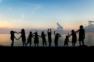 Silhouette of children on beach forming a heart shape