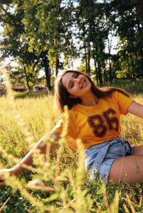 teen girl in yellow crew neck t shirt and blue denim shorts sitting on green grass field