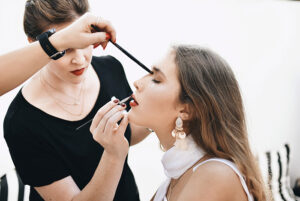 two people putting makeup on sitting woman