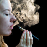 Woman exhaling smoke from an electronic vape